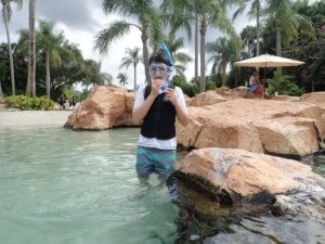 Boy with autism puts snorkeling mask on and gets in water