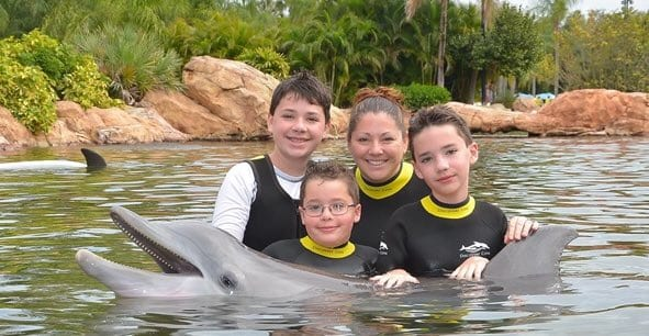 Family picture of successful trip to Discovery Cove with boy with autism