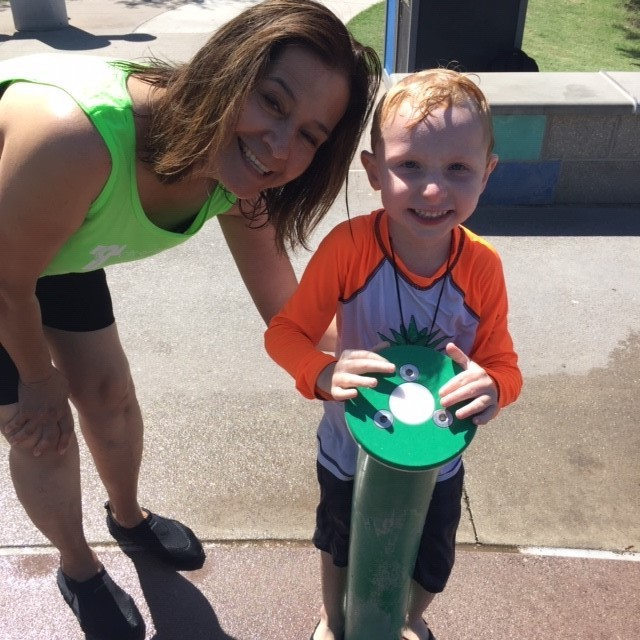 Staff member and young boy playing in water at Splash Pad at Kiwanis Park in Tempe