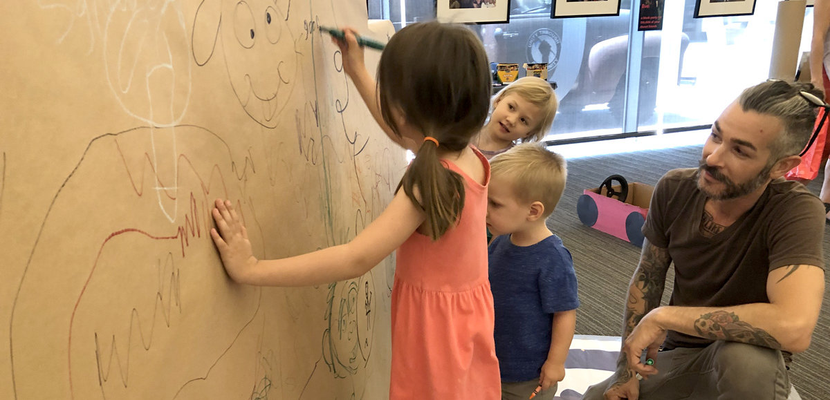 young kids drawing on paper wall at Tempe Public Library