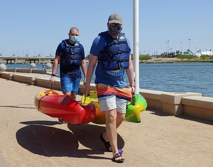 two kayakers heading to the water at Town Lake