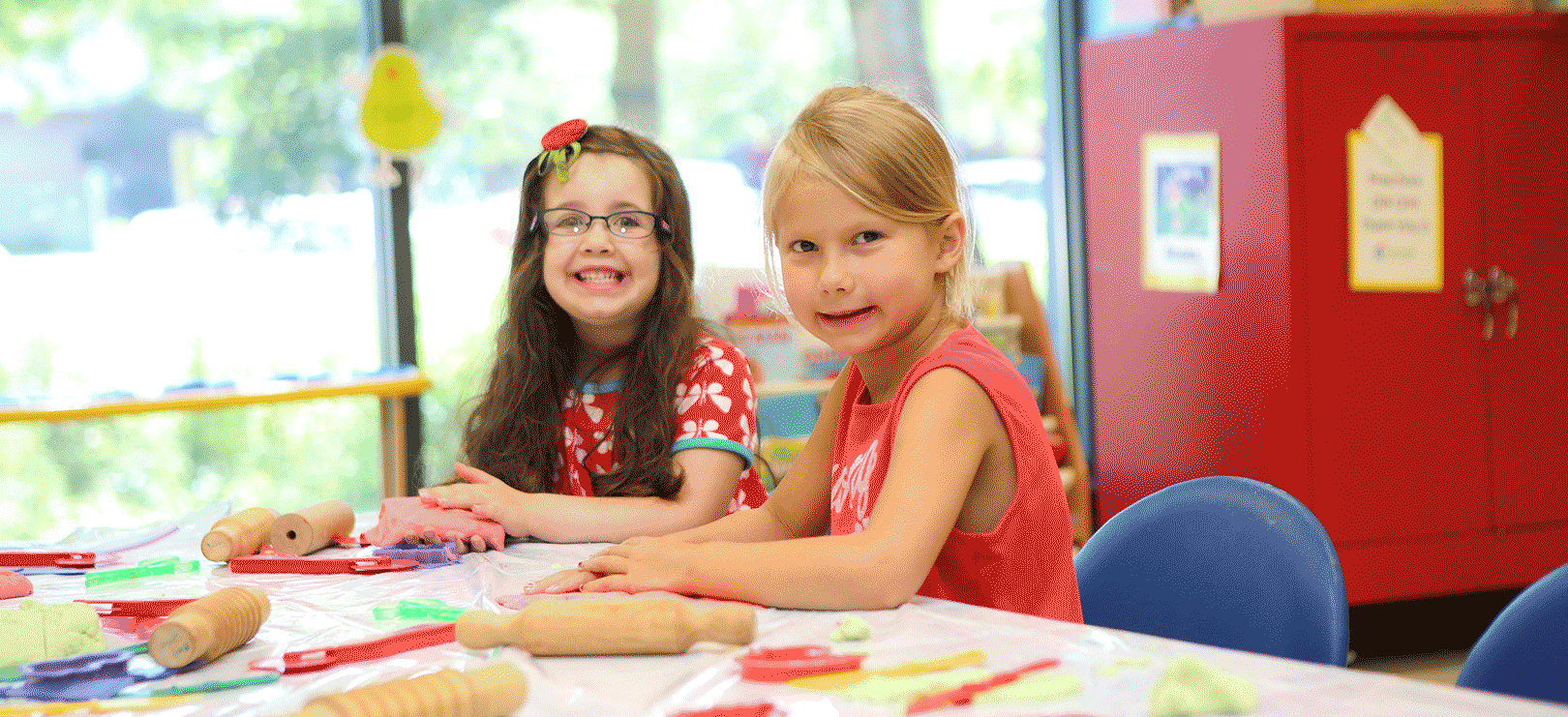 two young girls smiling while at Family Museum Summer camp activity table